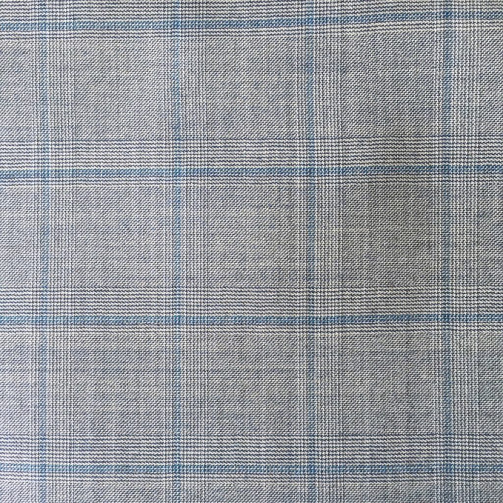 Hochwertigste Schurwollen S150 Qualität mit 15% Seidenbeimischung im klassischen Glencheck Dessin auf grauer Basis und trendigem hellblauen Gitterkaro